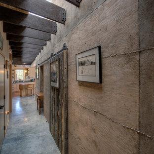 Rustik inredning av en hall, med betonggolv och bruna väggar