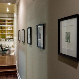 Idée de décoration pour un couloir design avec un mur gris et un sol en bois foncé.