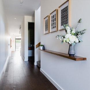 メルボルンの中サイズのコンテンポラリースタイルのおしゃれな廊下 (白い壁、ラミネートの床、茶色い床) の写真
