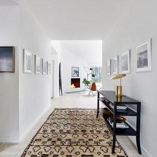 Idée de décoration pour un couloir nordique de taille moyenne avec un mur blanc, un sol en bois clair et un sol blanc.