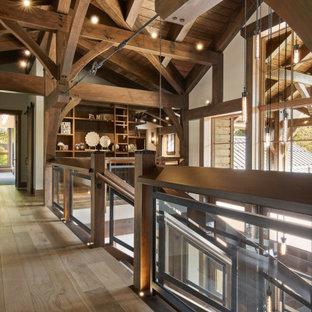 Пример оригинального дизайна: большой коридор в стиле рустика с светлым паркетным полом, бежевым полом и балками на потолке
