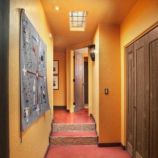 Aménagement d'un couloir campagne avec un mur orange, béton au sol et un sol rouge.
