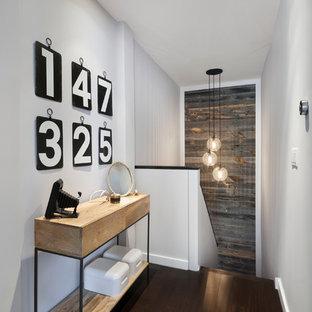 Inredning av en modern mellanstor hall, med vita väggar, mörkt trägolv och brunt golv