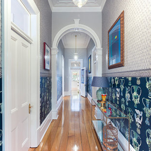 Inspiration for an eclectic hallway in Sydney with multi-coloured walls, medium hardwood floors and brown floor.