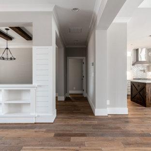 Uriger Flur mit beiger Wandfarbe, braunem Holzboden, freigelegten Dachbalken und Holzdielenwänden in Charlotte