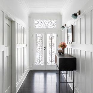 Cette photo montre un couloir chic avec un mur blanc, un sol marron, un plafond à caissons et du lambris.