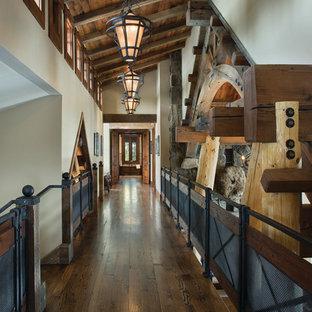 Ejemplo de recibidores y pasillos rurales con paredes blancas y suelo de madera oscura
