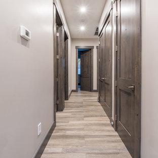 Exempel på en mellanstor modern hall, med grå väggar, laminatgolv och brunt golv