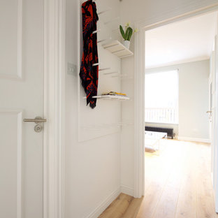 Exemple d'un petit couloir tendance avec un mur blanc et un sol en bois clair.