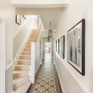 Klassisk inredning av en stor hall, med vita väggar, klinkergolv i keramik och flerfärgat golv