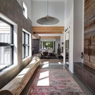 Réalisation d'un couloir design avec un mur blanc et béton au sol.