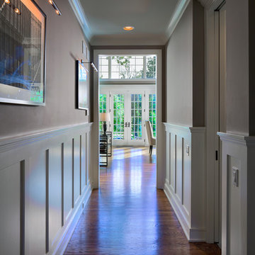 Entry hall with recessed panel wainscot walls enjoys view to backyard