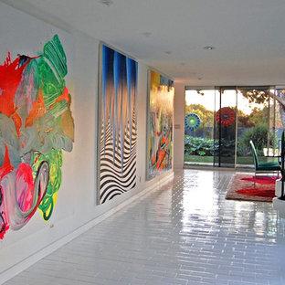 Idées déco pour un grand couloir contemporain avec un mur blanc, un sol en brique et un sol blanc.