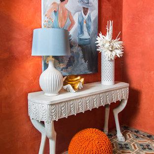 Cette photo montre un couloir méditerranéen de taille moyenne avec un mur orange et un sol en carrelage de porcelaine.