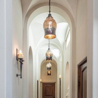 Пример оригинального дизайна: коридор в средиземноморском стиле с белыми стенами, темным паркетным полом и коричневым полом