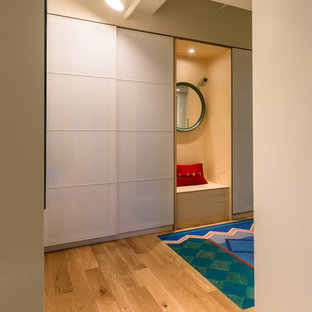 Cette image montre un couloir urbain avec un mur beige et un sol en bois clair.