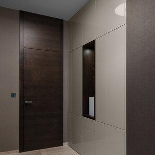 Cette image montre un grand couloir minimaliste avec un mur marron et un sol en marbre.