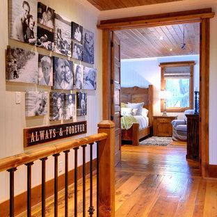 На фото: коридор в стиле рустика с белыми стенами и паркетным полом среднего тона с