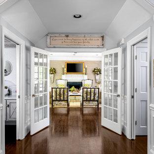 Cette photo montre un couloir chic de taille moyenne avec un mur gris, un sol en bois foncé, un sol marron, un plafond voûté et boiseries.