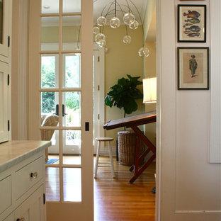 Idée de décoration pour un couloir tradition avec un mur beige, un sol en bois brun et un sol orange.