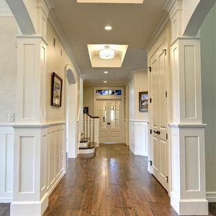 Imagen de recibidores y pasillos clásicos con paredes beige, suelo de madera en tonos medios y suelo marrón