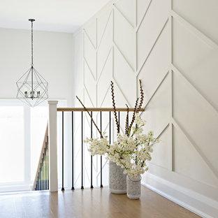 Esempio di un ingresso o corridoio country con pareti bianche e parquet chiaro