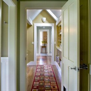 Idée de décoration pour un couloir champêtre avec un mur vert et un sol en bois brun.