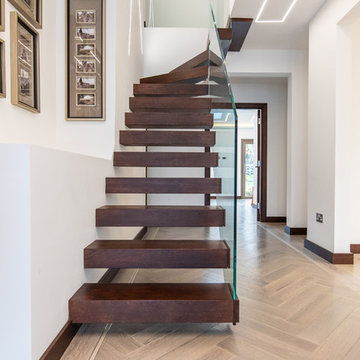 Floating stairs with frameless glass balustrade in chocolate brown colour