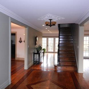 Idée de décoration pour un grand couloir tradition avec un mur vert et un sol en bois brun.