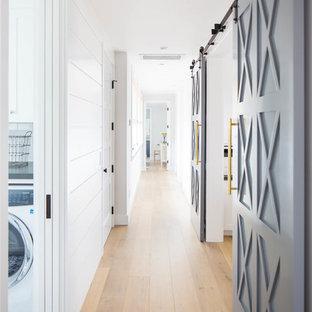 Aménagement d'un couloir campagne de taille moyenne avec un mur blanc, un sol en bois brun et un sol beige.