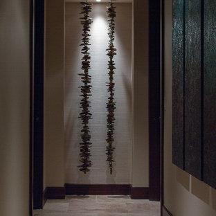 Idée de décoration pour un couloir bohème de taille moyenne avec un mur beige et un sol en carrelage de porcelaine.