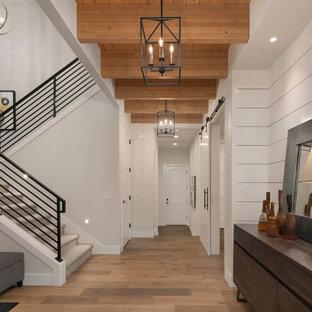 Aménagement d'un grand couloir campagne avec un mur blanc et un sol en bois brun.