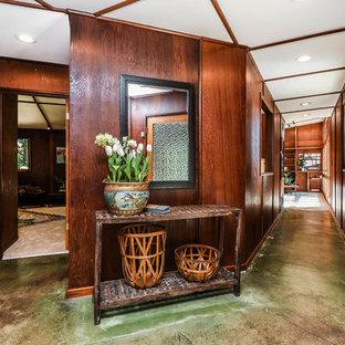 На фото: большие коридоры в стиле ретро с коричневыми стенами, бетонным полом и зеленым полом
