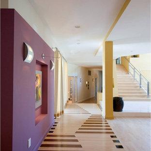 Inredning av en modern hall, med lila väggar, ljust trägolv och flerfärgat golv