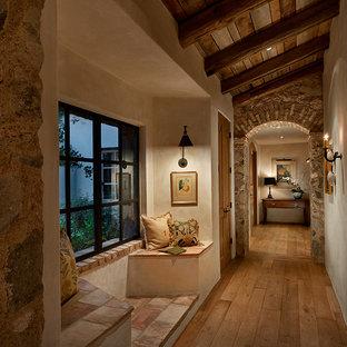 Inspiration for a mediterranean medium tone wood floor and brown floor hallway remodel in Phoenix with beige walls
