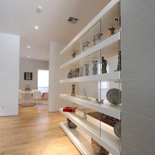 Foto på en mellanstor funkis hall, med vita väggar och ljust trägolv