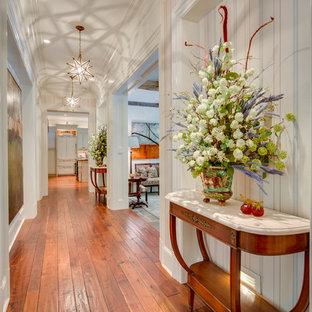 Aménagement d'un couloir classique de taille moyenne avec un mur blanc, un sol en bois brun et un sol orange.