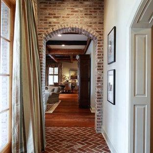 Rustik inredning av en mellanstor hall, med vita väggar, tegelgolv och rött golv