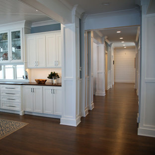 Design ideas for a mid-sized beach style hallway in Milwaukee with white walls, medium hardwood floors, brown floor, exposed beam and panelled walls.