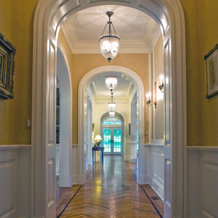 Inspiration for a large timeless light wood floor hallway remodel in New York with yellow walls
