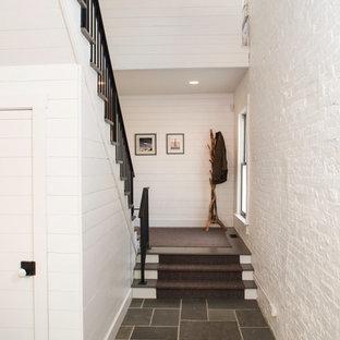 コロンバスの中サイズのインダストリアルスタイルのおしゃれな廊下 (白い壁、スレートの床) の写真