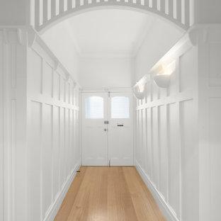 Aménagement d'un couloir contemporain de taille moyenne avec un mur blanc, un sol en bois clair, un sol beige et boiseries.