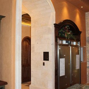 Immagine di un ingresso o corridoio mediterraneo di medie dimensioni con pareti arancioni, pavimento in travertino e pavimento beige