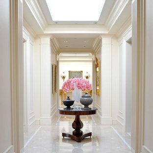 Стильный дизайн: огромный коридор в классическом стиле с белыми стенами и мраморным полом - последний тренд