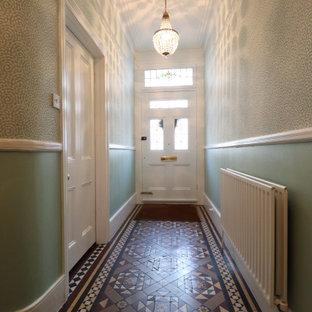 Bild på en mycket stor vintage hall, med gröna väggar, heltäckningsmatta och beiget golv