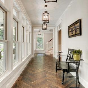 Cette image montre un couloir traditionnel avec un mur blanc, un sol en bois foncé et un sol marron.