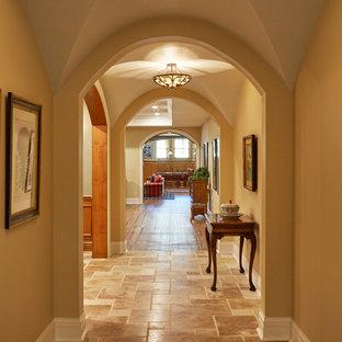 Ispirazione per un grande ingresso o corridoio tradizionale con pareti arancioni, pavimento in pietra calcarea e pavimento marrone