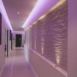 Cette image montre un couloir minimaliste de taille moyenne avec un mur blanc, un sol en carrelage de porcelaine et un sol beige.