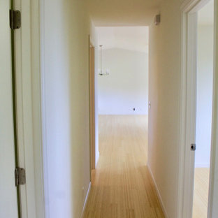Design ideas for a mid-sized beach style hallway in Hawaii with white walls, bamboo floors and beige floor.