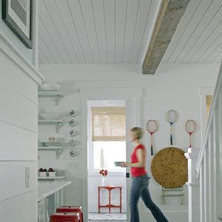 Maritim inredning av en hall, med vita väggar och skiffergolv